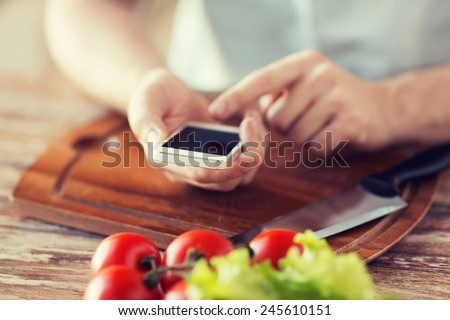 cooking, technology and home concept - closeup of man pointing finger to smartphone - stock photo