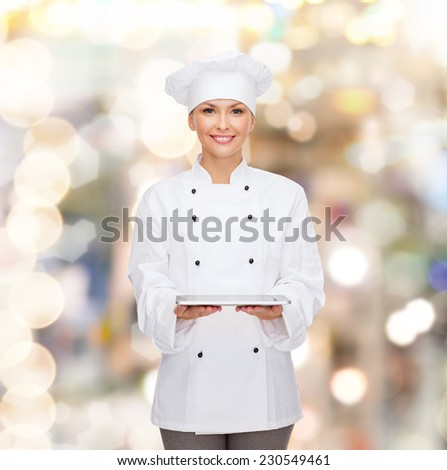 cooking, technology and people concept - smiling female chef, cook or baker with tablet pc computer over holidays lights background - stock photo