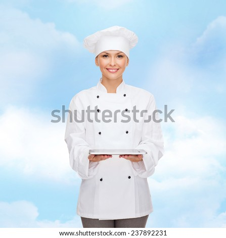 cooking, technology and people concept - smiling female chef, cook or baker with tablet pc computer over blue cloudy sky background - stock photo