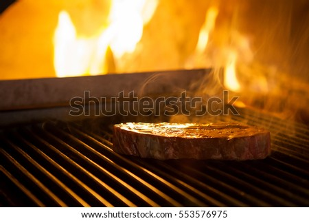 cooking the meat on the grill in the fireplace in the restaurant