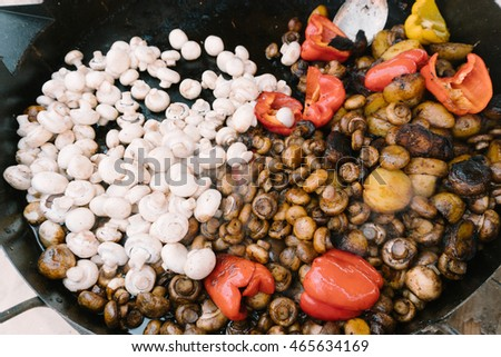 cooking the mushrooms in a large cooking pan with vegetables
