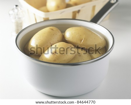 Cooking the potatoes in a saucepan of boiling water - stock photo