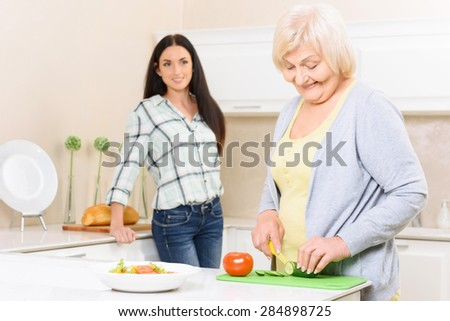 Cooking time. Pretty old woman standing in kitchen and cutting cucumber near her granddaughter. - stock photo