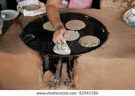 Cooking tortillas in Mexico on a clay and natural gas heated stove - oven. - stock photo