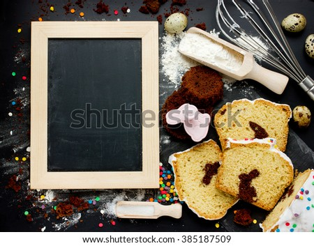 Cooking traditional Easter biscuits background. Festive funny bunny cake with ingredients on black table top view with space for text recipe on the chalkboard - stock photo