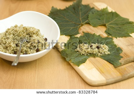 cooking Turkish food stuffed grape leaves with rice and spices - stock photo