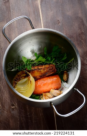 Cooking vegetable stock with roasted vegetables: carrots, garlic, parsley, onion and celery. Top view - stock photo