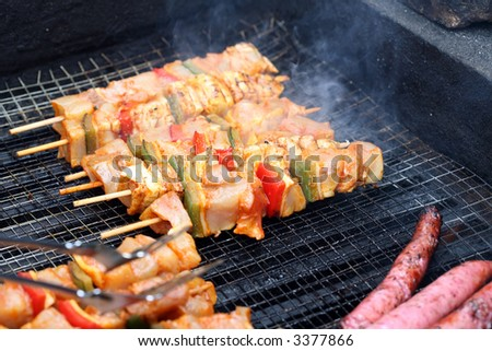 cooking white and red sausage on outdoor barbecue