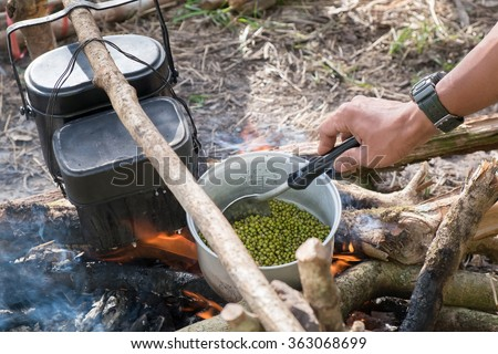 cooking with army pot on bonfire with orange flames and firewood