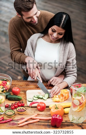 Cooking with love. Top view of beautiful young couple preparing food together and smiling - stock photo