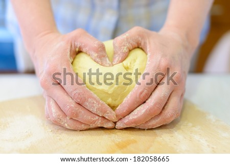 Cooking: woman hands kneading dough, close-up shot, fingers forms heart shape - stock photo