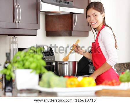 Cooking woman in kitchen stirring in pot making food for dinner. Young housewife smiling happy looking at camera. Mixed-race Caucasian / Asian chinese woman in her twenties. - stock photo