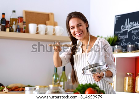 Cooking woman in kitchen with wooden spoon - stock photo