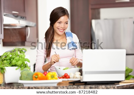 Cooking woman looking at computer while preparing food in kitchen. Beautiful young multiracial woman reading cooking recipe or watching show while making salad. - stock photo