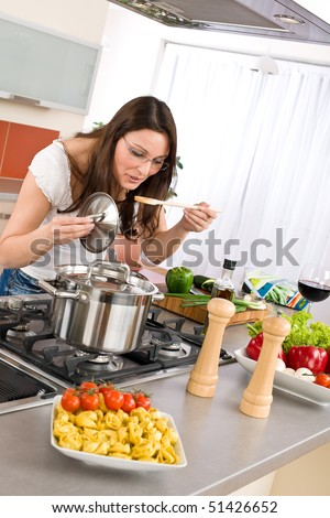 Cooking - Young woman in modern kitchen - stock photo