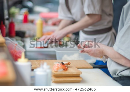 Cooks making japanese susi in open restaurant kitchen