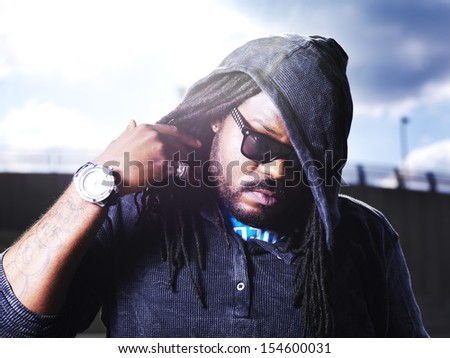cool african man showing dreads with lens flare - stock photo