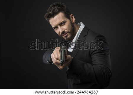 Cool aggressive man in shirt and jacket pointing a gun - stock photo