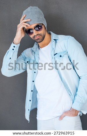 Cool and calm. Handsome young man in eyewear and headwear posing against grey background - stock photo