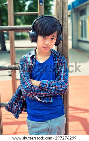 Cool Asian boy listening to music on headphones - stock photo