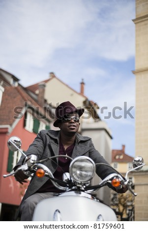 Cool, attractive black man riding retro scooter with smart clothes through old city. - stock photo