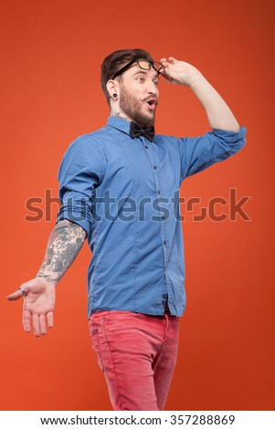 Cool bearded hipster is very surprised. He is standing and gesturing. The guy is touching his eyeglasses and looking forward with shock. Isolated - stock photo