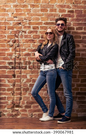 Cool beautiful young couple in leather jackets and sunglasses is looking at camera, posing and smiling, standing against brick wall