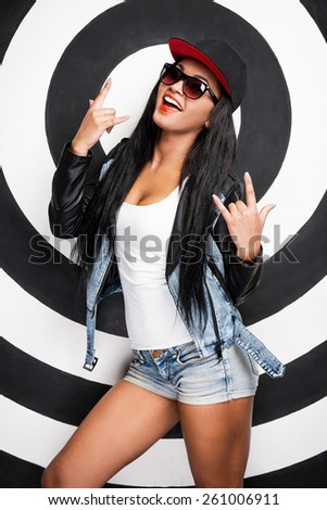 Cool beauty. Cheerful young African woman in baseball cap posing against black and white background - stock photo
