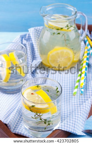 Cool beverage with lemon and thyme in a tray on blue wooden background - stock photo