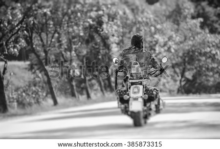 Cool biker with long hair riding motorcycle on road. View from the back. Tilt shift lens blur effect. Black and white - stock photo