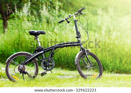 Cool black folding bicycle in nature - stock photo