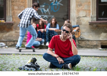 Cool boy posing sitting on the street smiling - stock photo