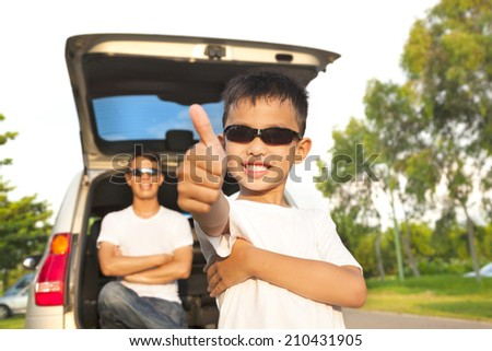 cool boy thumb up and father across arms with car  - stock photo