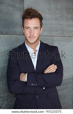 Cool business man leaning on urban wall outdoors