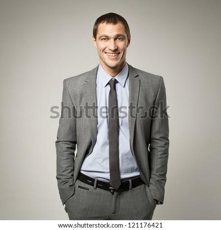 Cool businessman portrait on grey background - stock photo
