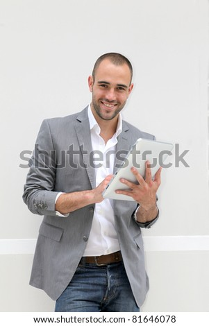 Cool businessman using electronic tablet on white background - stock photo