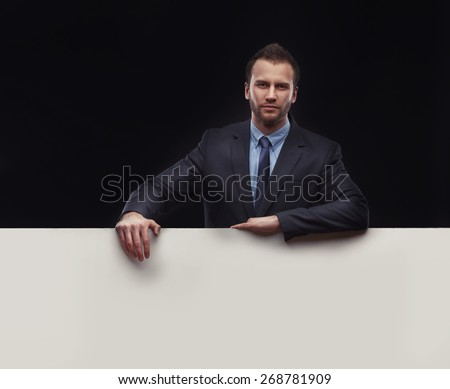 Cool businessman with copyspace standing on dark studio background - stock photo