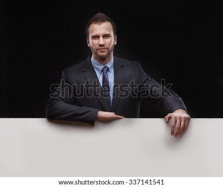 Cool businessman with copyspace standing on dark studio background