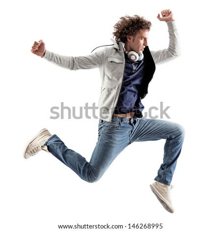 Cool Caucasian man with headphones around his neck jumping.