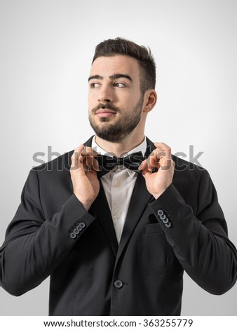 Cool confident relaxed man adjusting bow tie looking away. Desaturated portrait over gray studio background with retro vignette.