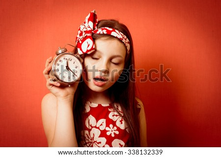 cool cute little girl with an alarm clock in the morning - stock photo