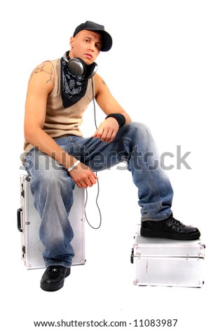 Cool DJ Is Relaxing Young man sitting on dj cases with headphones and lots of tattoos. - stock photo