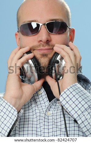 Cool DJ with Headphones in front of blue Background - stock photo