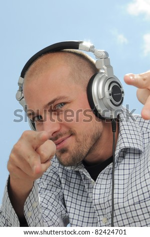 Cool DJ with Headphones pointing at you - stock photo