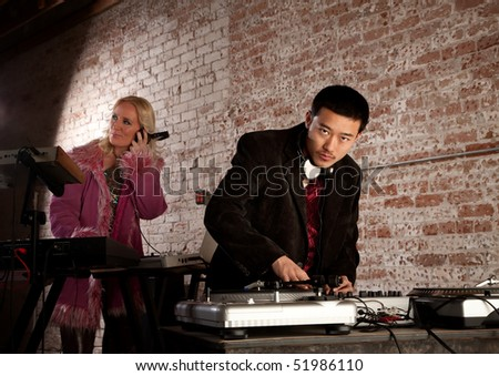 Cool DJ with turntable and blonde keyboardist - stock photo