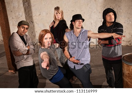 Cool ethnically diverse break dancers in underground setting - stock photo