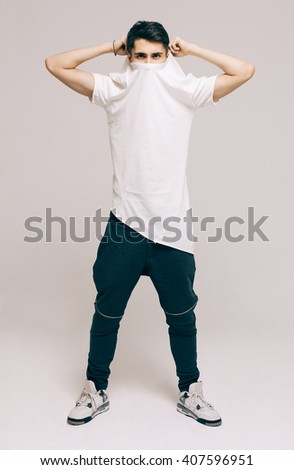 Cool fashion male model posing. Street youth fashion. Studio. Indoor. - stock photo