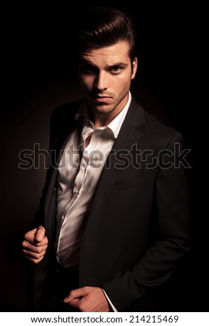 cool fashion man in suit pulling his coat in a fashion pose, in studio - stock photo