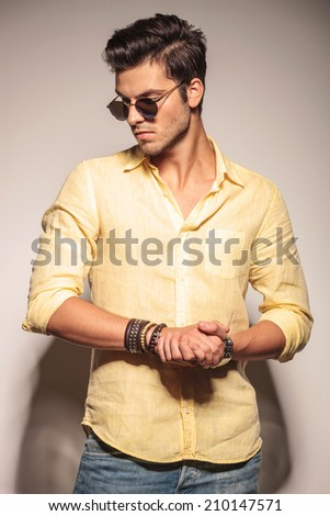 cool fashion model with palms together and sunglasses looking at the camera - stock photo
