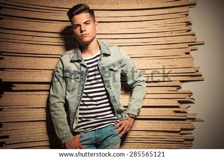cool fashion young man looking relaxed , against wood background in studio - stock photo